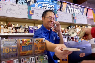 With previous store winner banners behind him, Kien Lo sells lottery tickets Monday. With Saturday's jackpot, Lichine's Liquor and Deli inspires a new degree of awe.